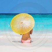 Девушка под зонтиком от солнца на пляже